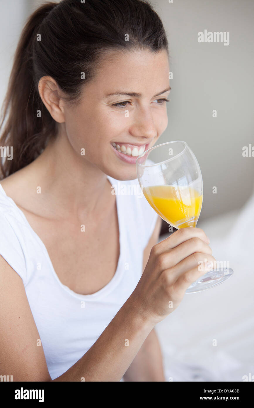Young woman drinking glass of orange juice - Stock Image