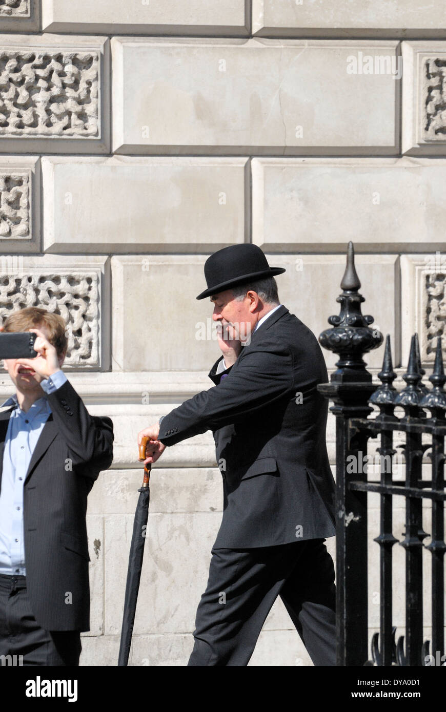 London, England, UK. City gent in a bowler hat on mobile phone in the street Stock Photo