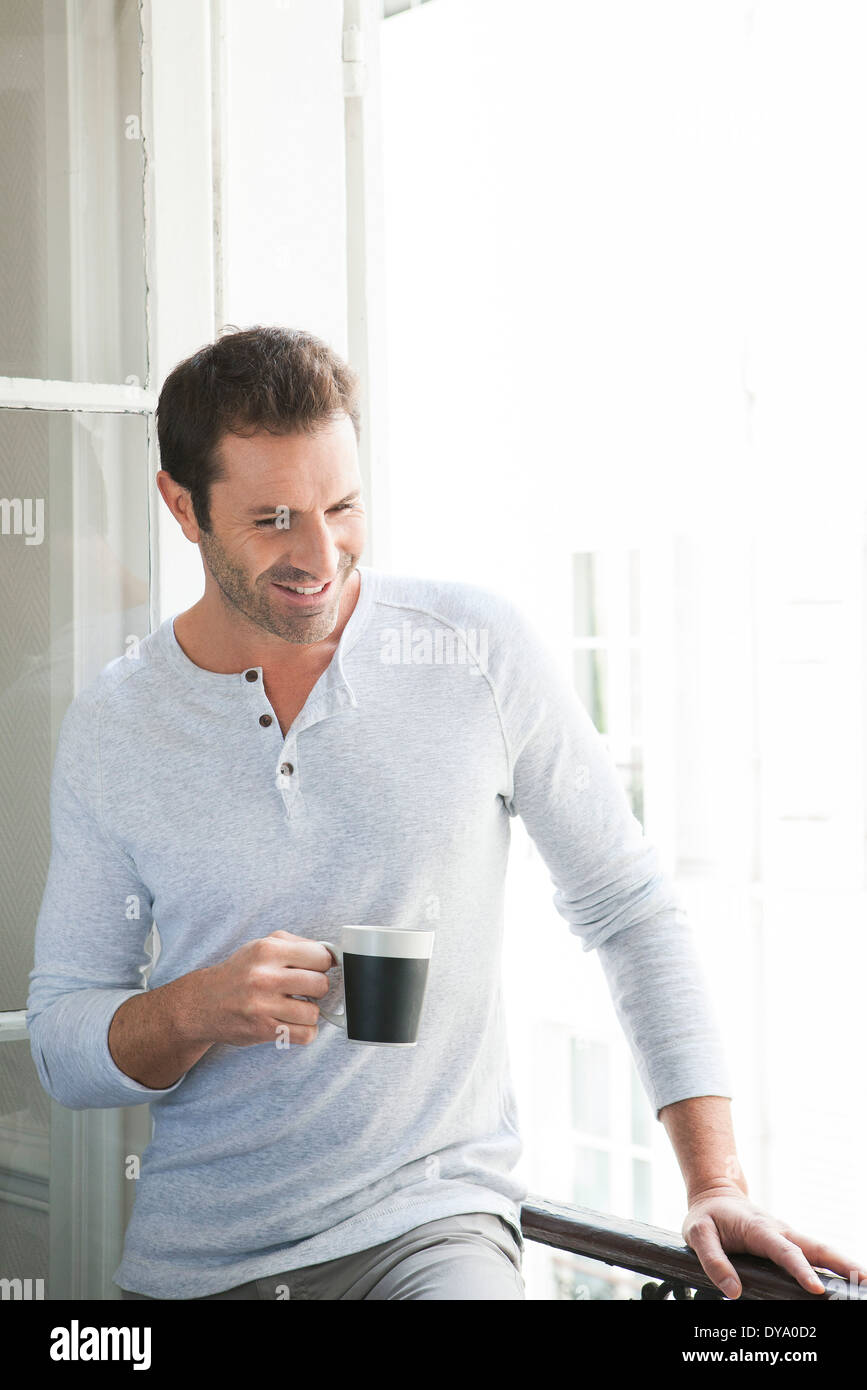 Man standing by window with mug in hand - Stock Image