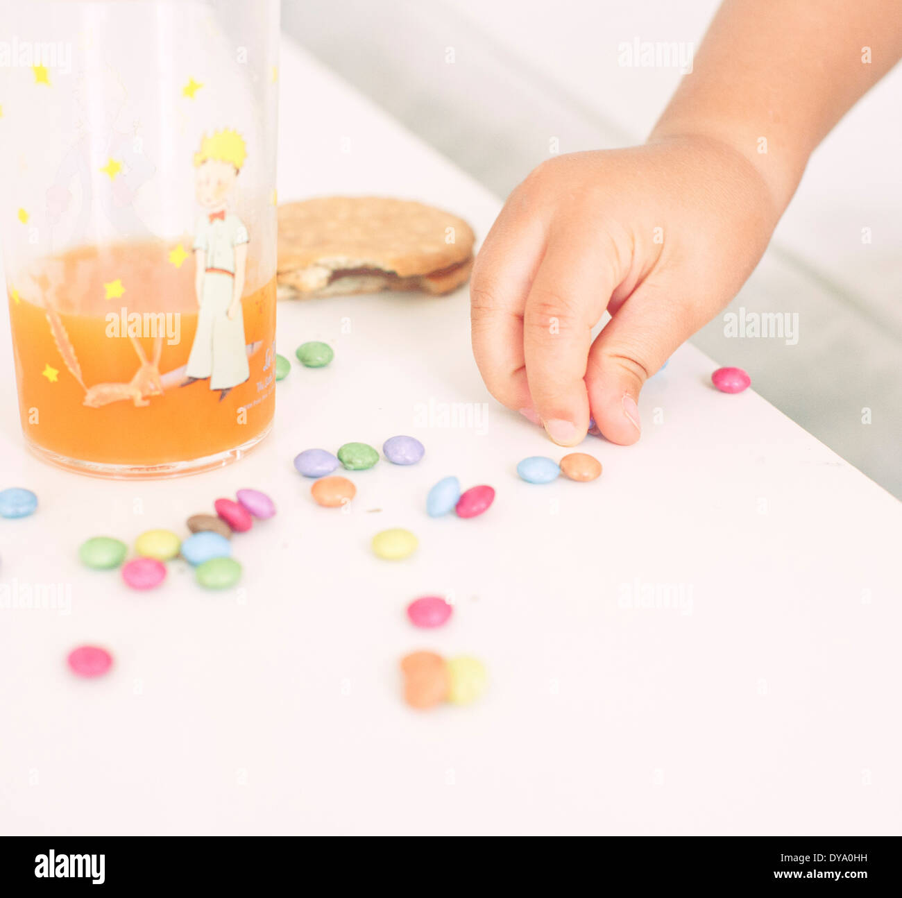 Child picking up candies from table - Stock Image