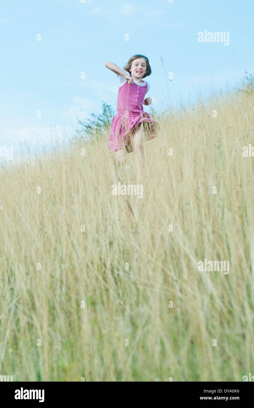 Girl running through tall grass - Stock Image