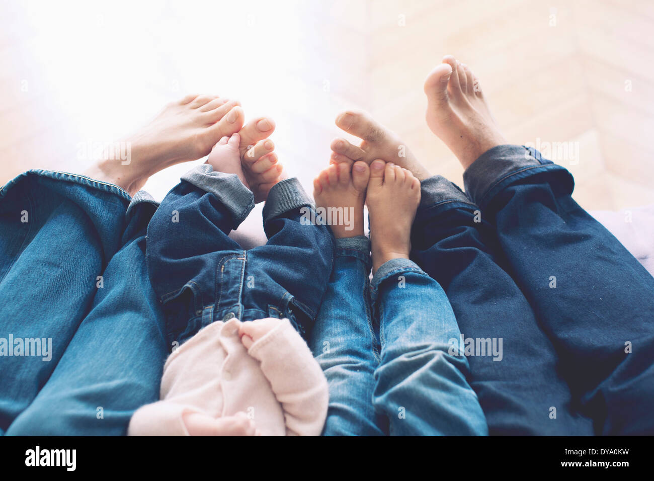 Outstretched legs and barefeet of family with two children - Stock Image