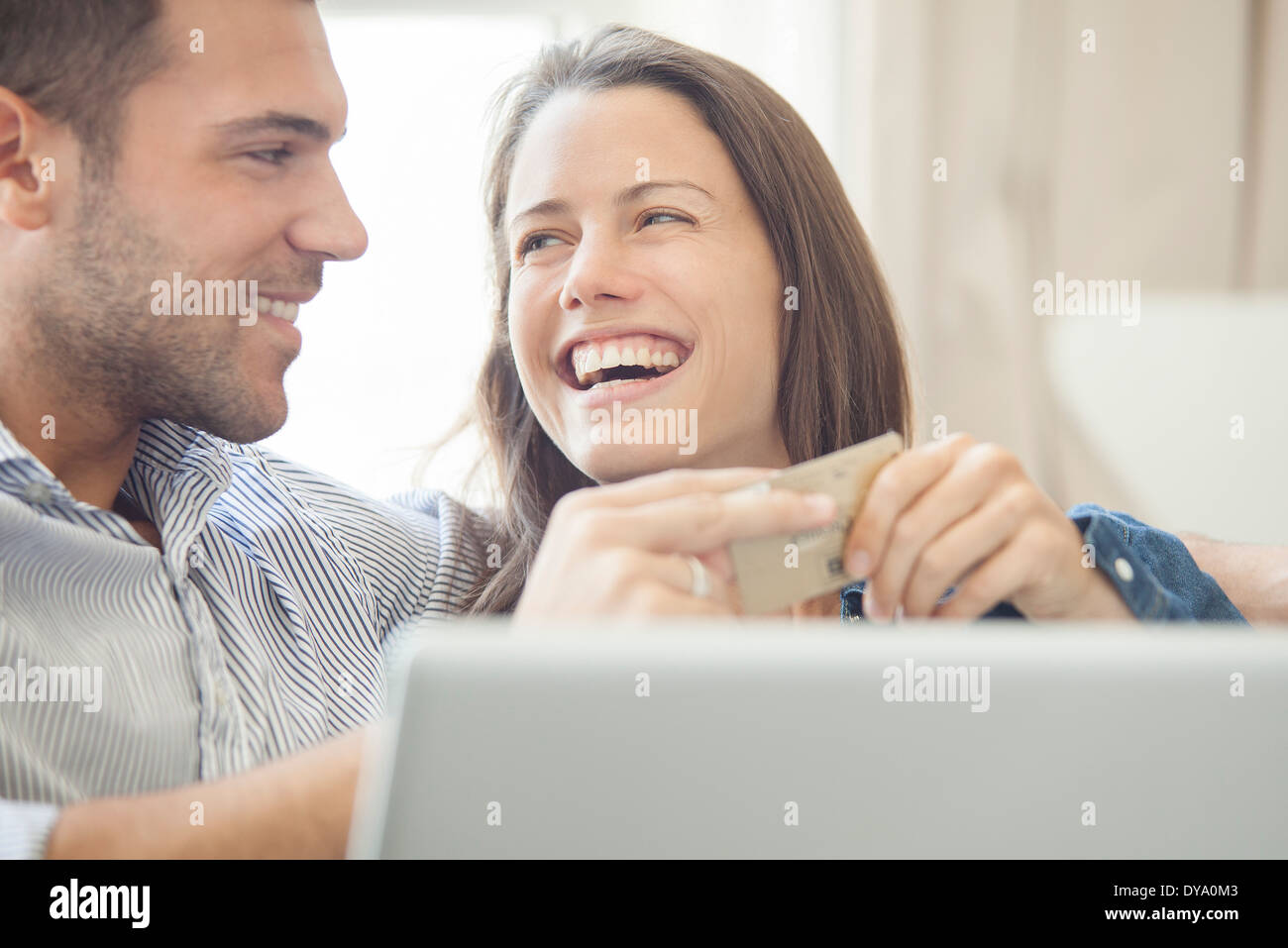 Couple at home shopping online together - Stock Image