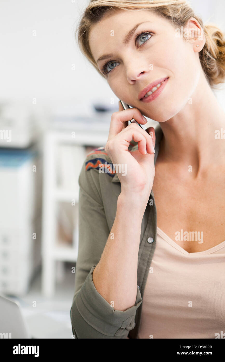 Woman talking on cell phone, head tilted - Stock Image