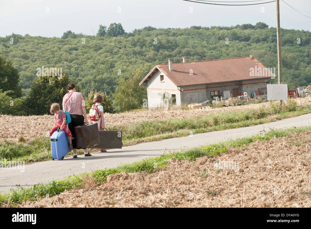 Mother and children wandering through countryside, dragging suitcases behind them - Stock Image