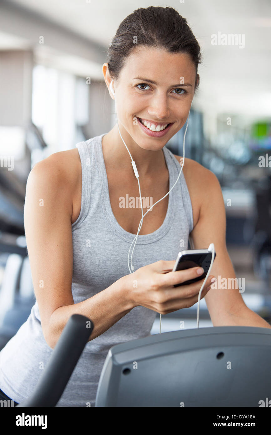 Young woman listening to music while using step climber at gym - Stock Image