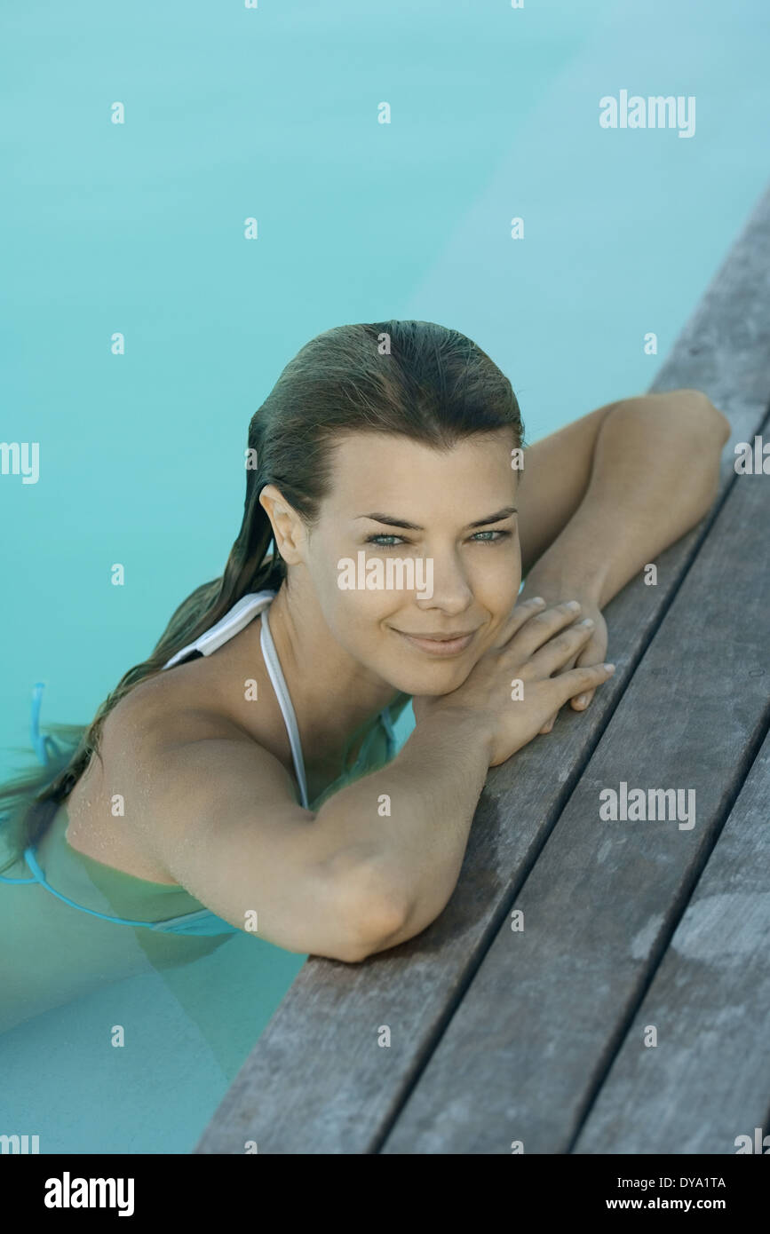Young woman leaning on poolside, smiling - Stock Image