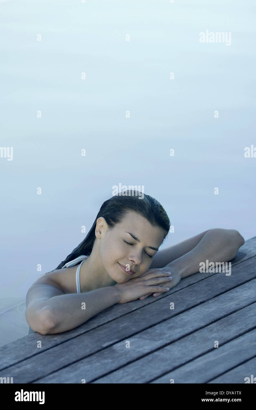 Woman in pool leaning against deck, resting head on arms, eyes closed - Stock Image