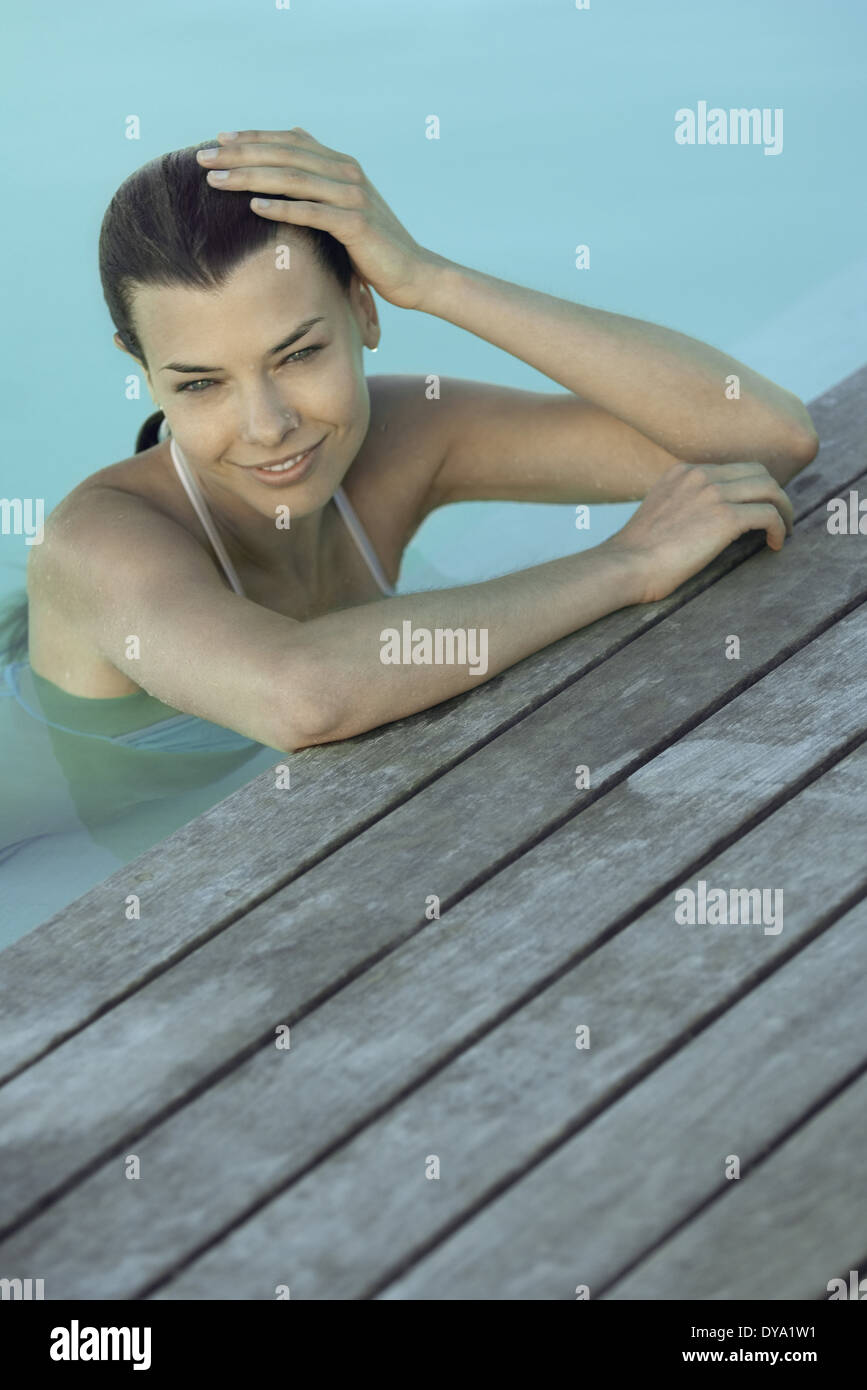 Woman in pool leaning against deck, holding head, smiling - Stock Image
