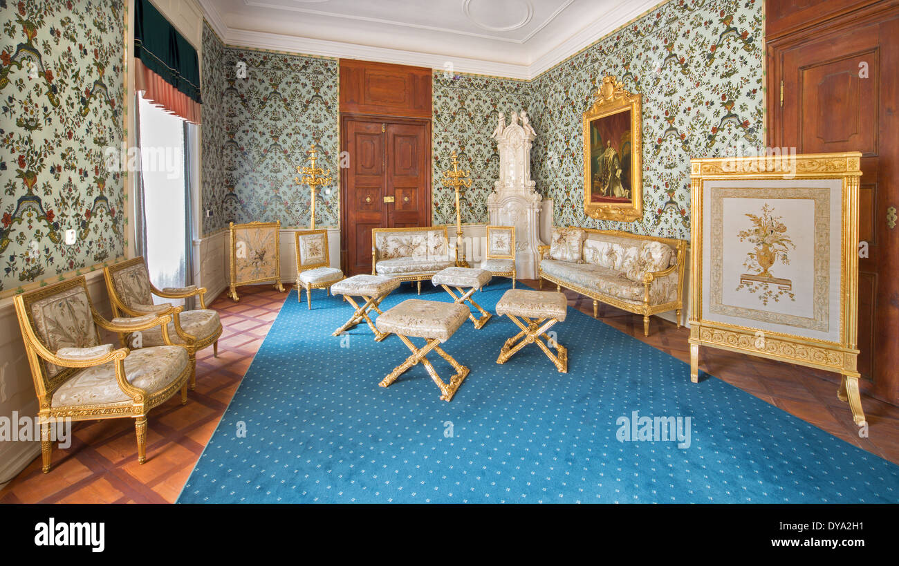 Golden saloon with the polychrome in lime wood carved furniture from 18. cent. in palace Saint Anton. - Stock Image