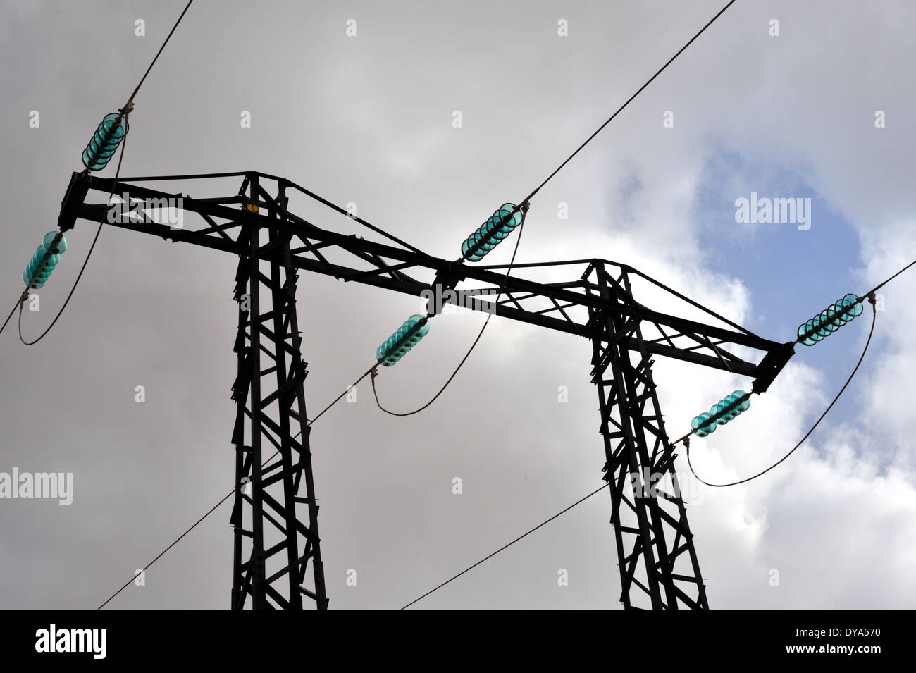 High voltage three phase electrical power lines with glass insulators at top of pylon - Stock Image