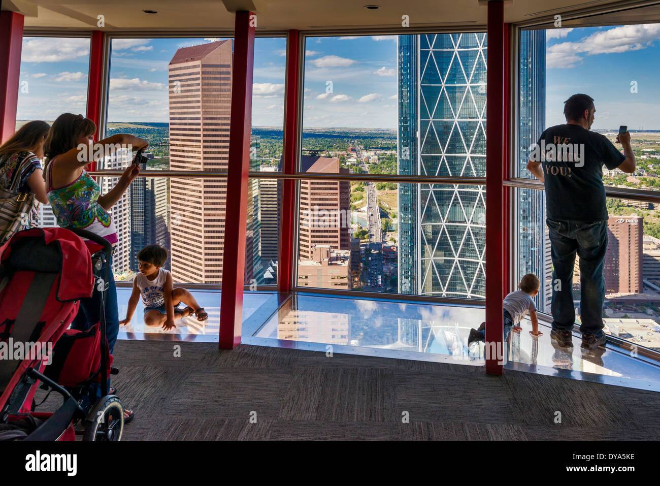 Visitors Looking At Downtown Standing On Glass Floor At Calgary