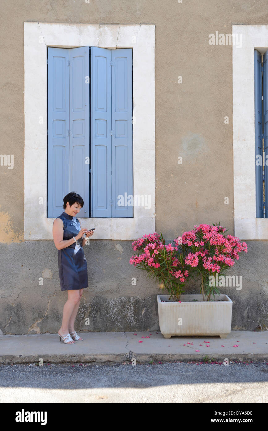 Europe, France, Provence, cell phone, woman, window, brunette, french, urban, chic, Villars - Stock Image