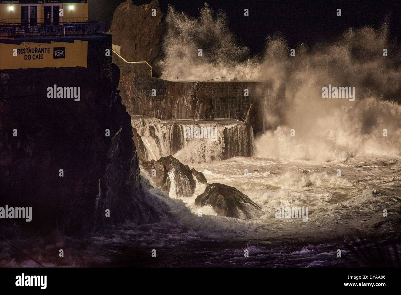 Storm waves hitting coastline by night Stock Photo