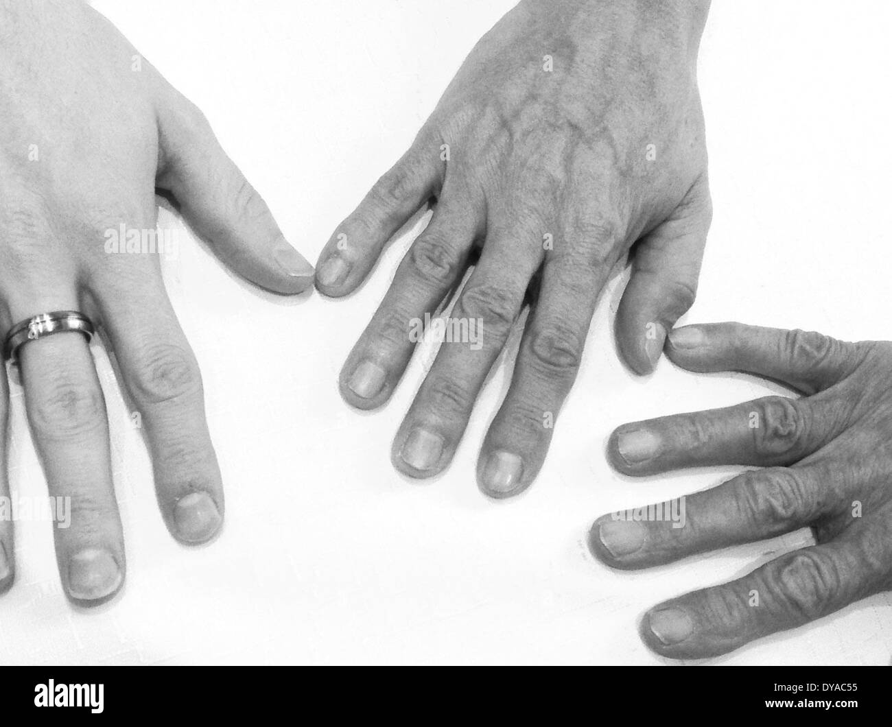 The hands of grandfather, son and grandson on a table. April 2014 Stock Photo