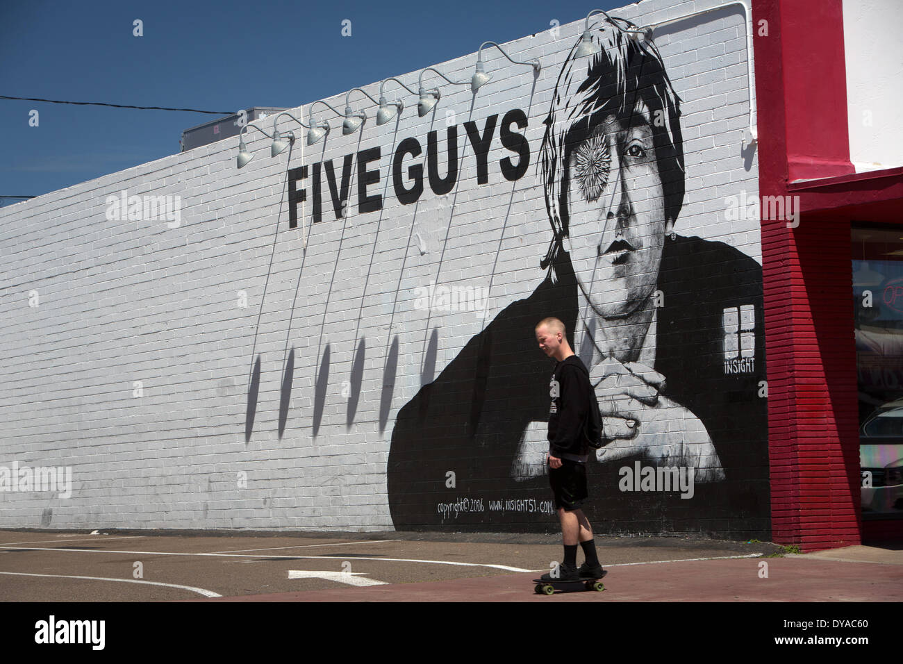 Skater in front of a John Lennon mural on the wall of a Five Guys burger restaurant, in April 2014. - Stock Image