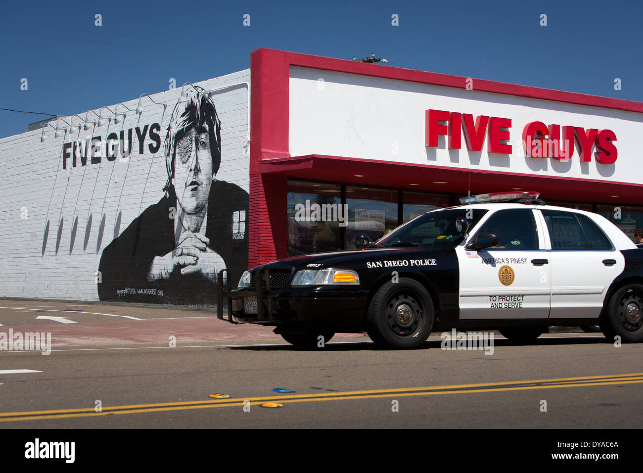 Police cruiser in front of a Five Guys burger restaurant with a John Lennon mural, in April 2014. - Stock Image
