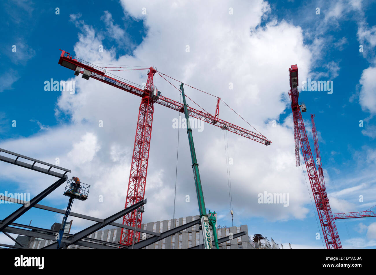 Steel erector standing on an access platform, and tower cranes on a construction site, First Street, Manchester, England, UK - Stock Image