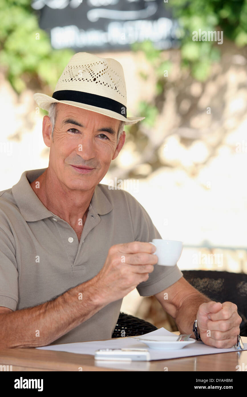 62dd8bbf57a39 65 years old man wearing a straw hat and drinking a tea cup on a cafe  terrace