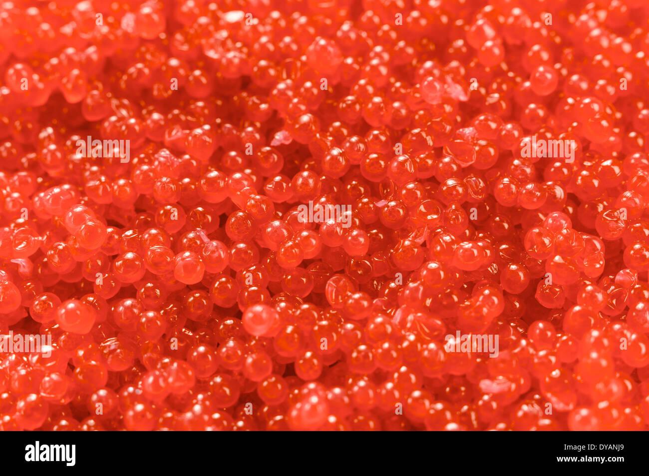 Red caviar closeup. The eggs are small. - Stock Image