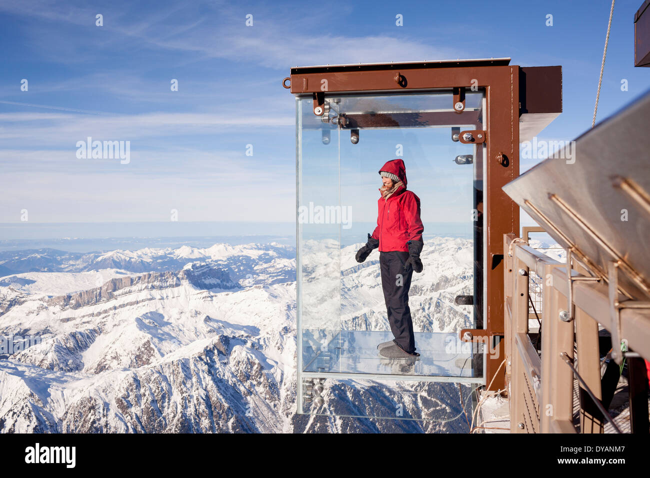 A tourist stands in the 'Step into the Void' glass box on the Aiguille Du Midi (3842m) mountain top above Chamonix Mont-Blanc - Stock Image