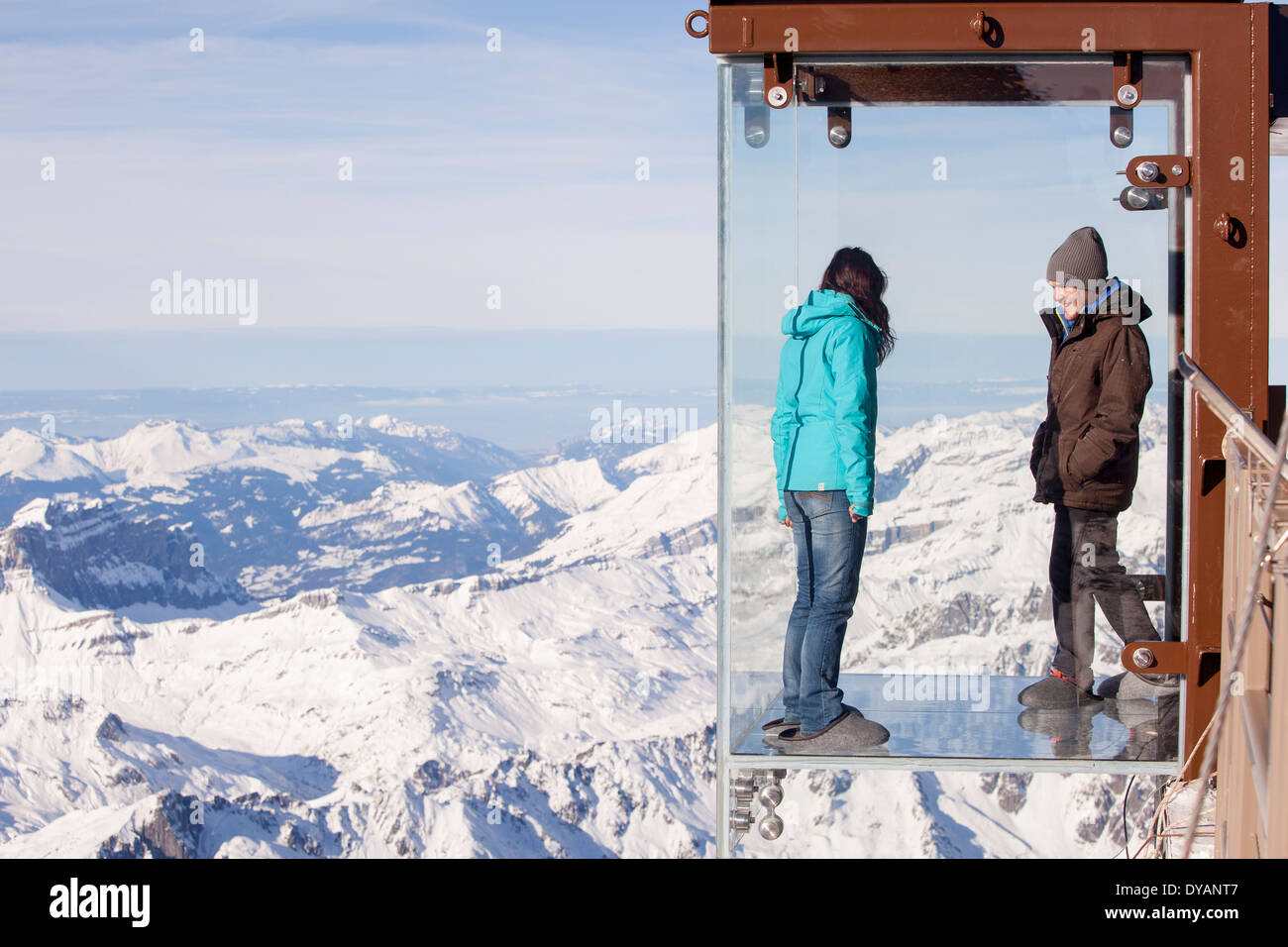 Tourists stands in the 'Step into the Void' glass box on the Aiguille Du Midi (3842m) mountain top above Chamonix Mont-Blanc - Stock Image