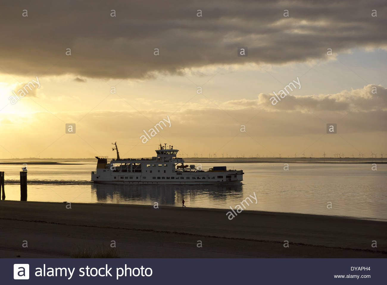 The ferry Frisia V departs Nordseeinsel Norderney toward Norddeich, wind generators in distance. Stock Photo
