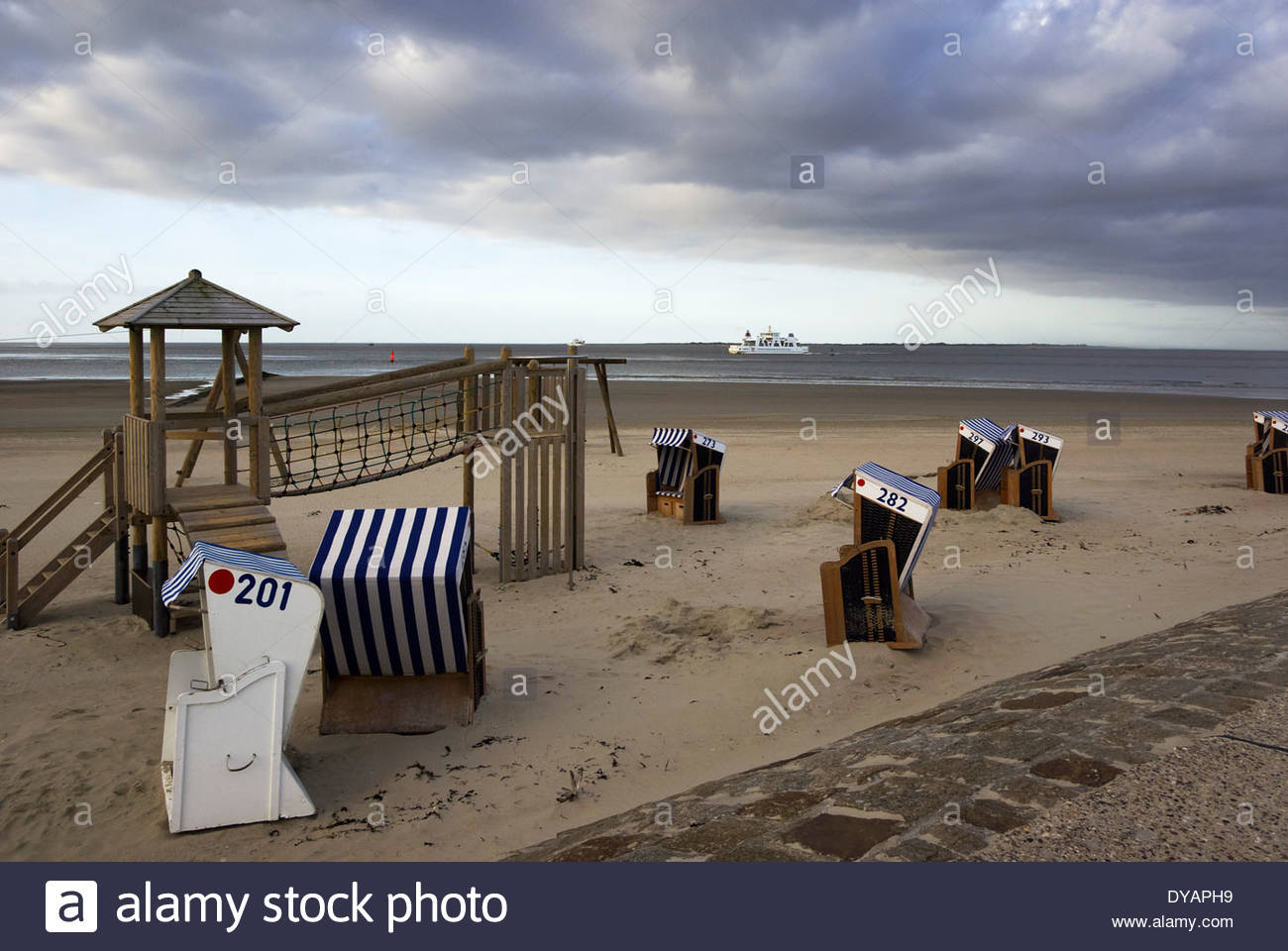 Beach chairs and recreation await the day's vacationing families, as ferries come and go in the distance, Norderney, Stock Photo