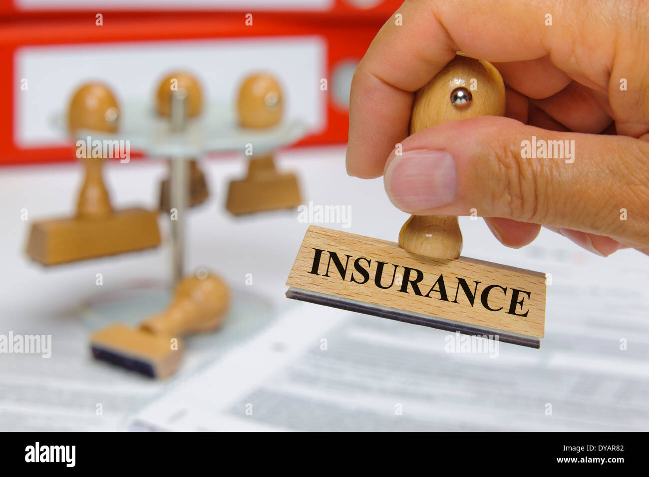 insurance marked on rubber stamp in hand - Stock Photo