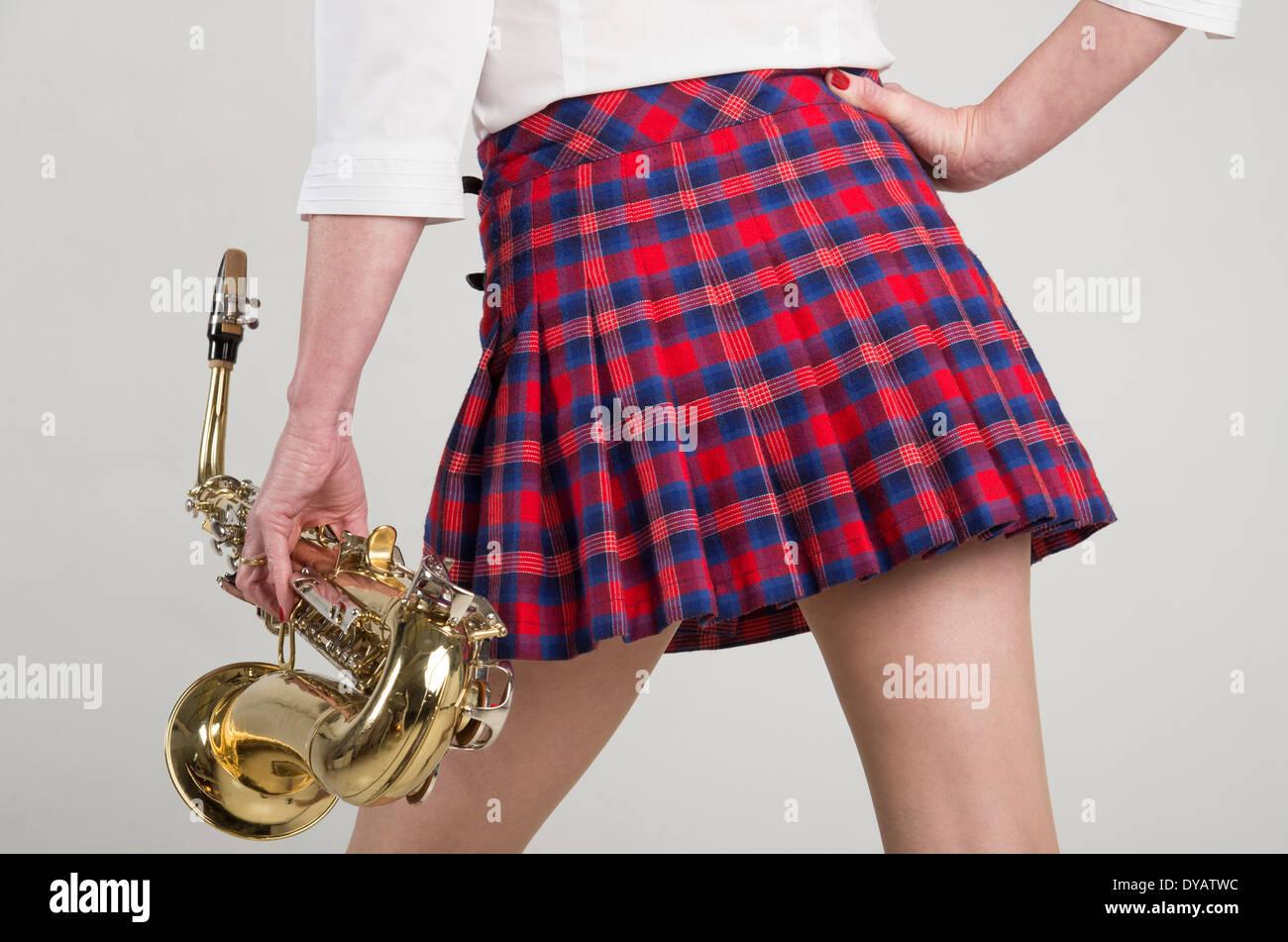 Woman In Short Tartan Skirt Carrying A Saxophone Sax