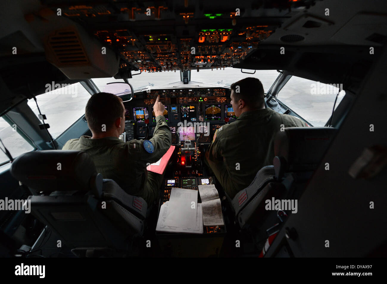 Nick Horton, left, and Lt. Clayton Hunt, naval aviators assigned to Patrol Squadron (VP) 16, perform preflight checks in the flight station of a P-8A Poseidon prior to a mission to assist in search and rescue operations for Malaysia Airlines flight MH370. VP-16 is deployed in the U.S. 7th Fleet area of responsibility supporting security and stability in the Indo-Asia-Pacific region. (U.S. Navy photo by Chief Mass Communication Specialist Keith DeVinney/Released) - Stock Image