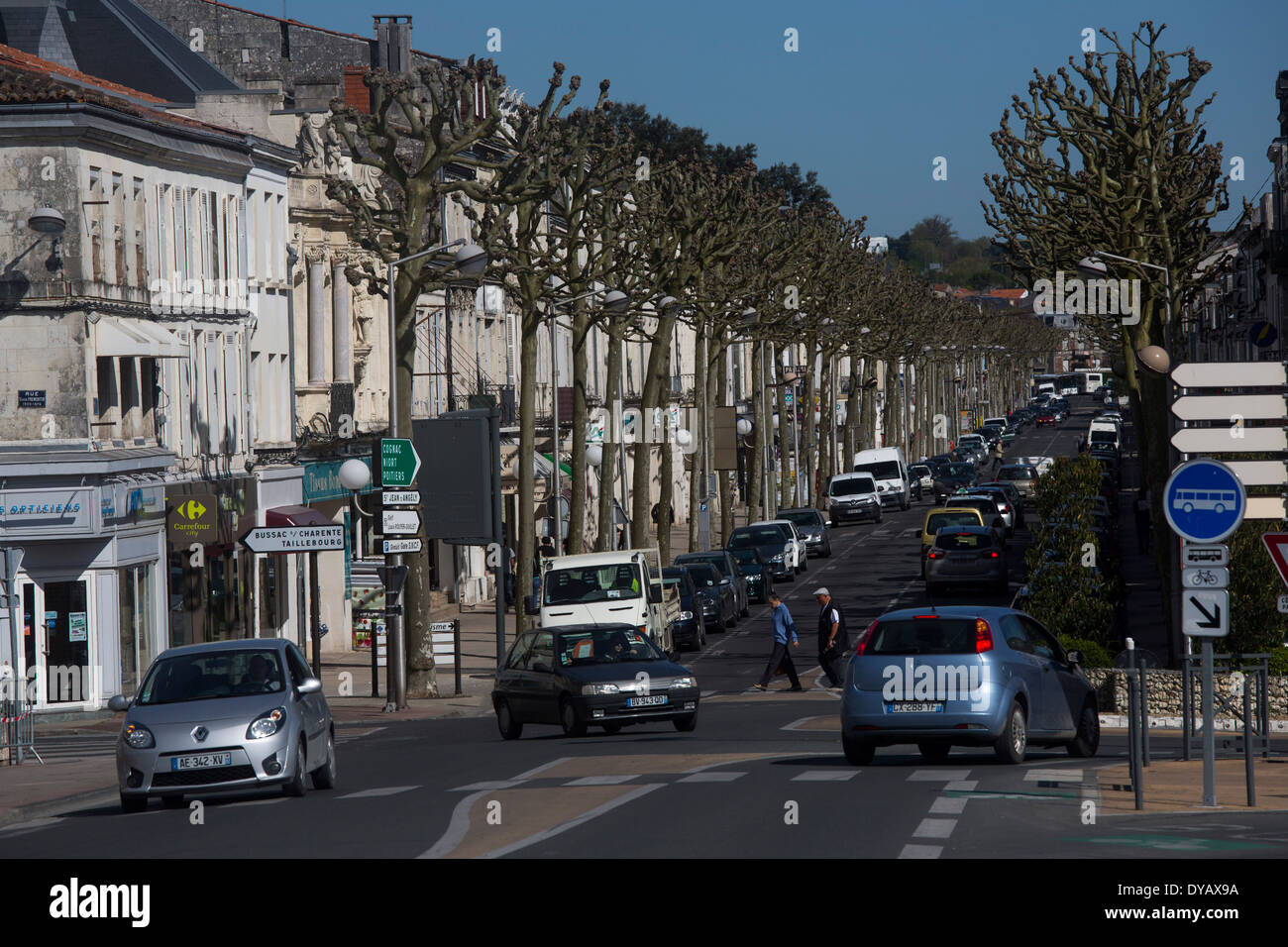 Main street lined with trees in medium sized town - Stock Image