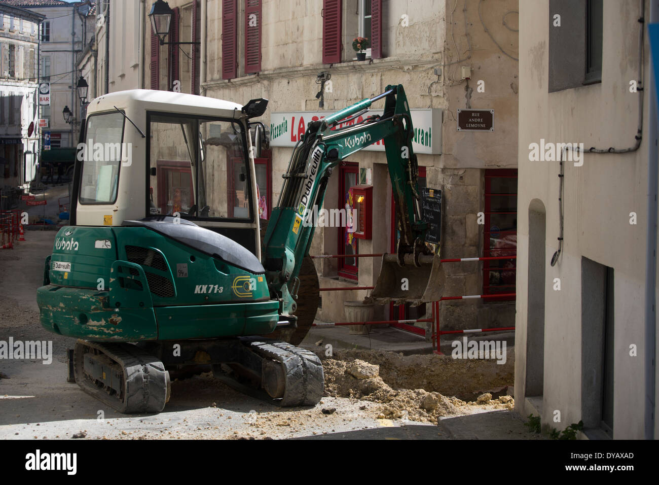 Digger excavating road outside cafe pavement - Stock Image