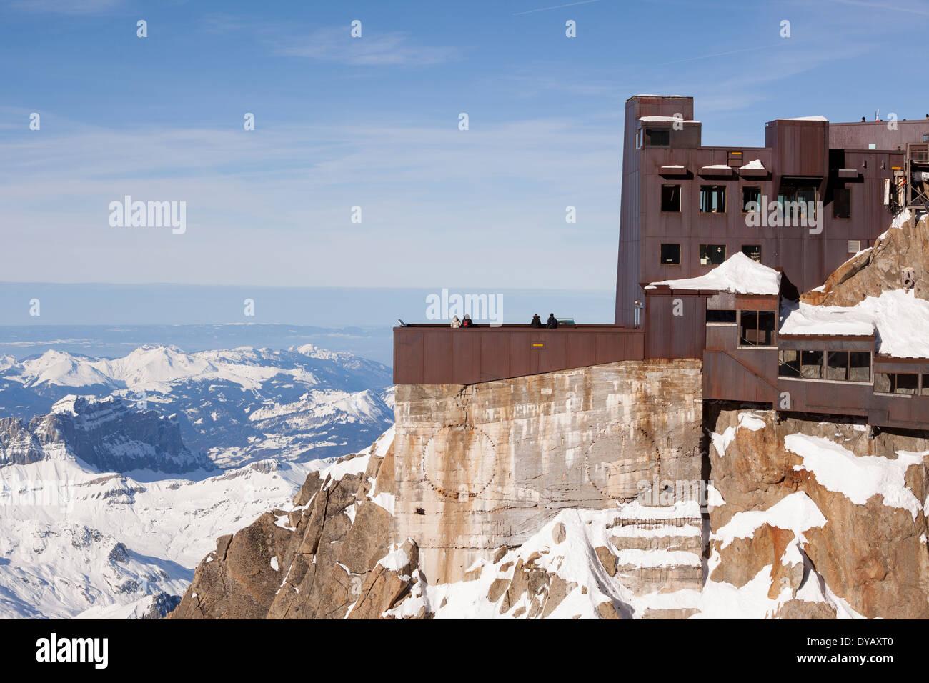 Tourists visit the lookout point building on the Aiguille Du Midi (3842m) mountain top above Chamonix Mont-Blanc. - Stock Image