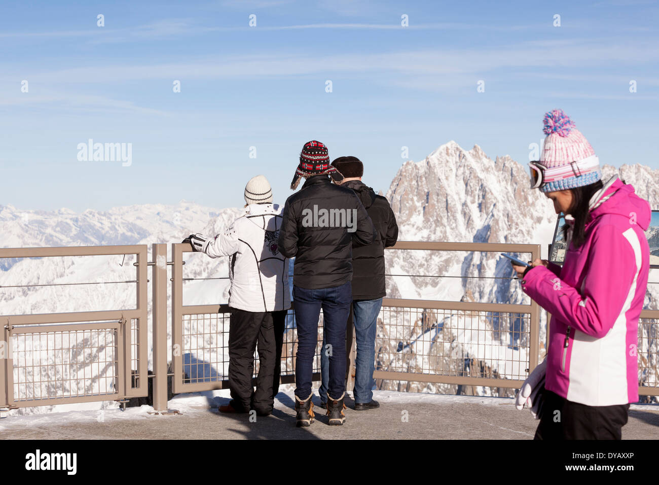 Tourists take photographs while visiting the Aiguille Du Midi (3842m) mountain top lookout point above Chamonix Mont-Blanc. - Stock Image