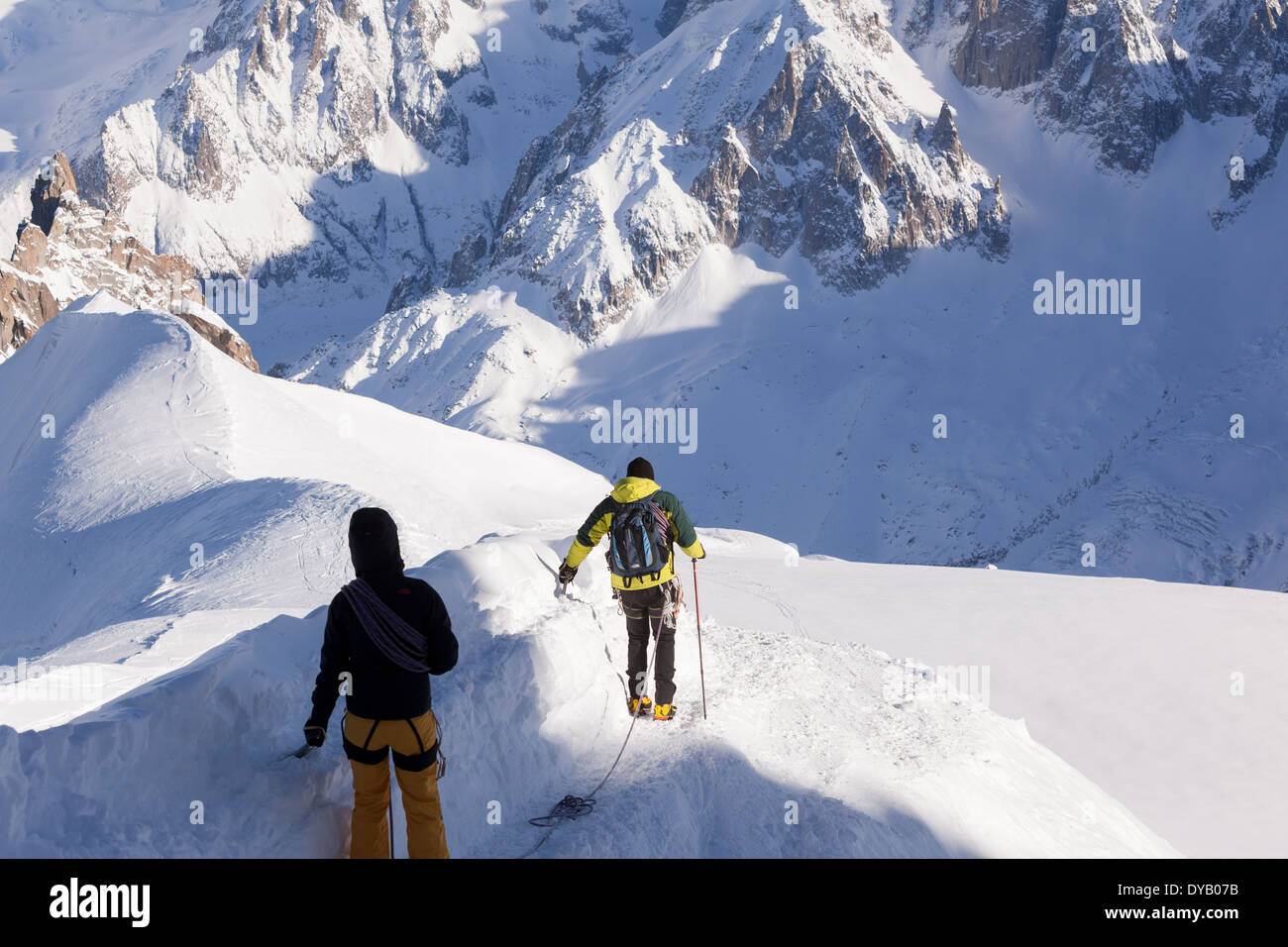 Mountaineers descend from a lookout point on the Aiguille Du Midi (3842m) mountain top above Chamonix Mont-Blanc. Stock Photo