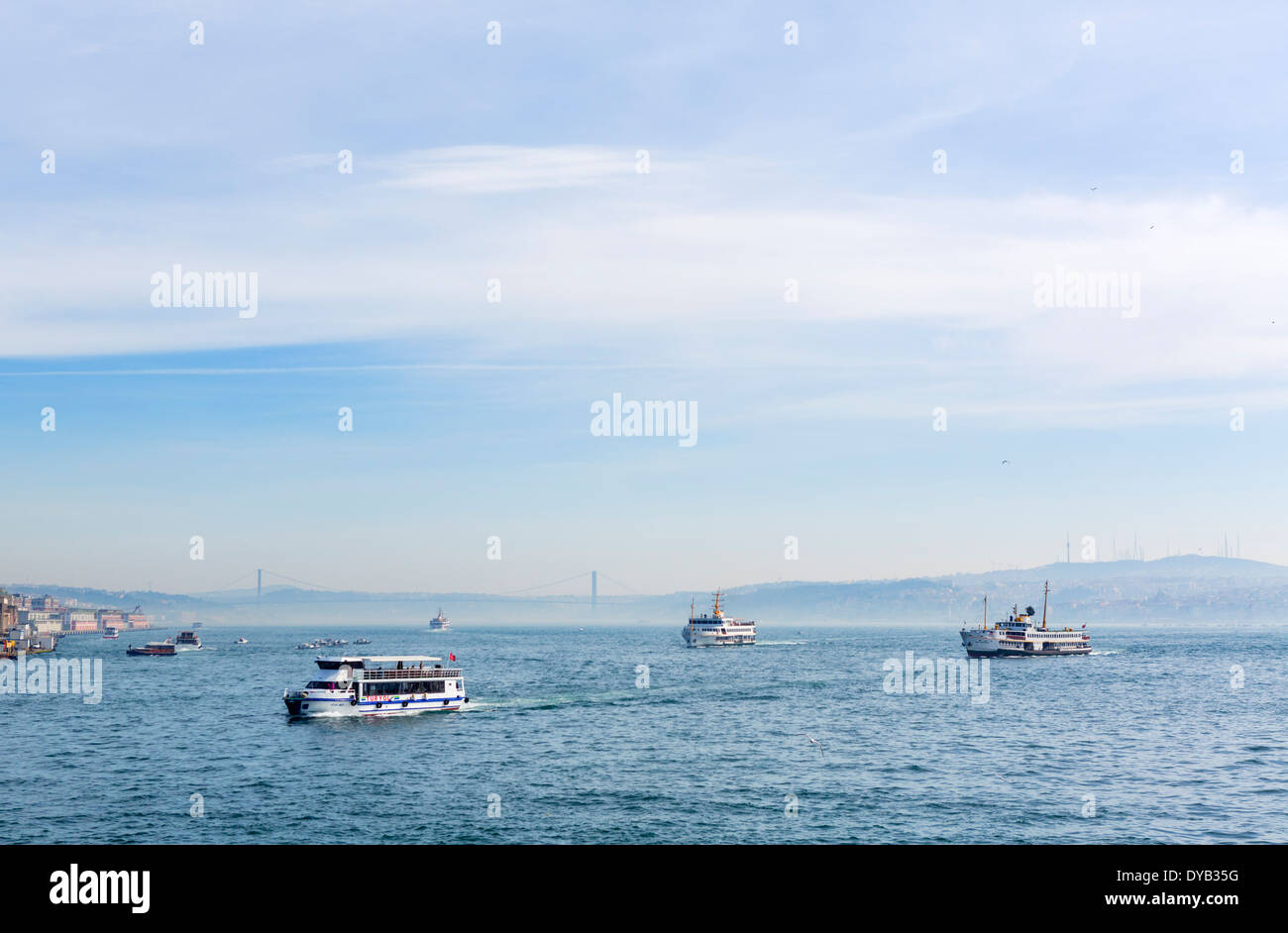 View of local ferries and tour boats on the Golden Horn looking towards the Bosphorus Bridge, Istanbul, Turkey - Stock Image