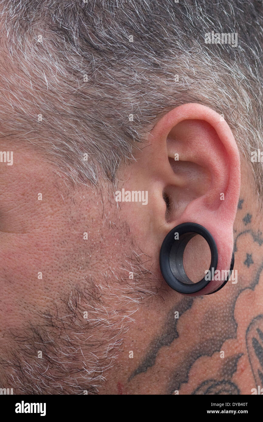 side view of a man with a stretched ear lobe and Tattoos Stock Photo