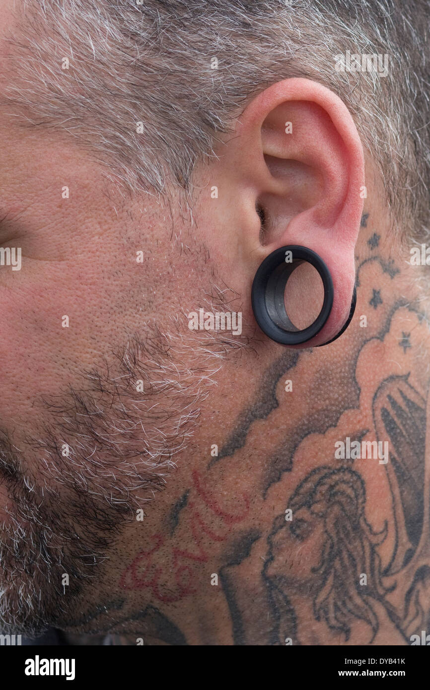 side view of a man with a stretched ear lobe and Tattoos - Stock Image