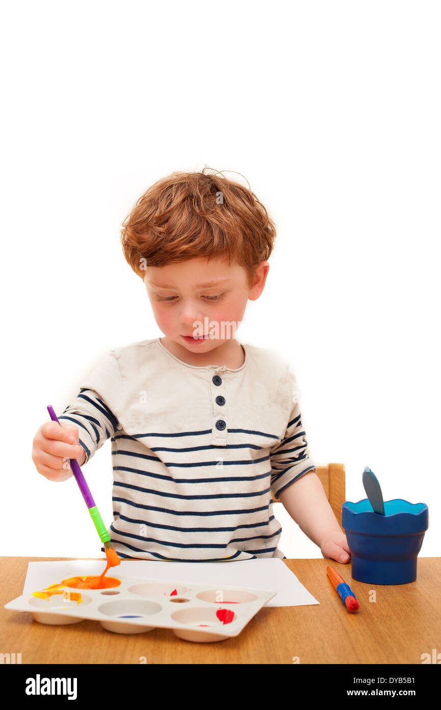 Auburn haired boy painting isolated background - Stock Image