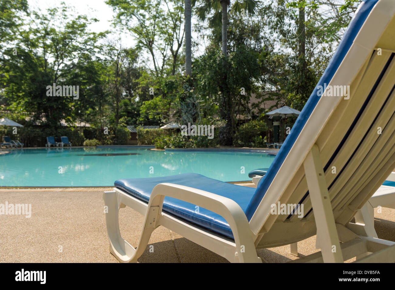 Unoccupied sunbed by the pool with nobody in daylight - Stock Image
