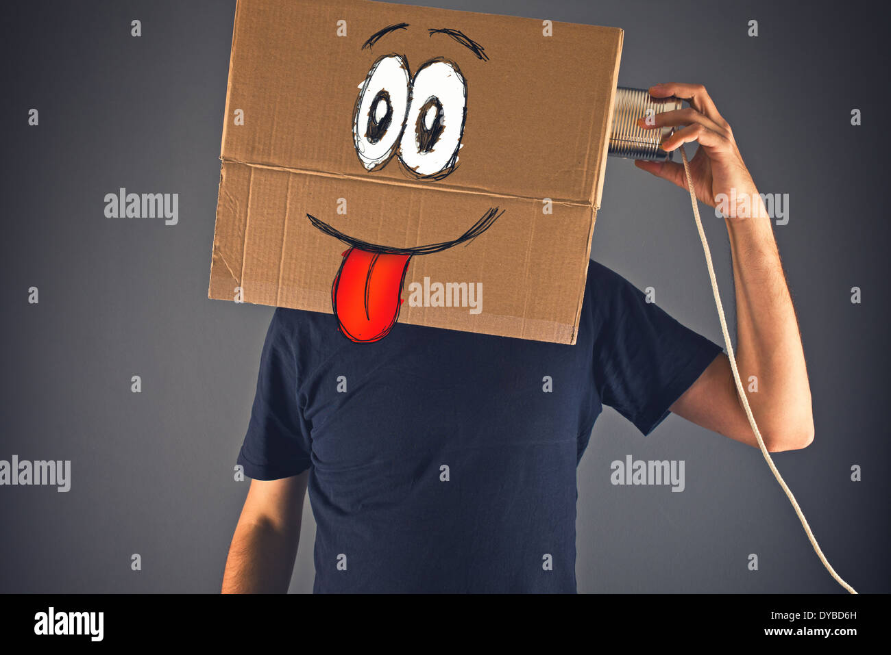 Man with cardboard box on his head using tin can telephone for conversation. Happy face expression. Stock Photo