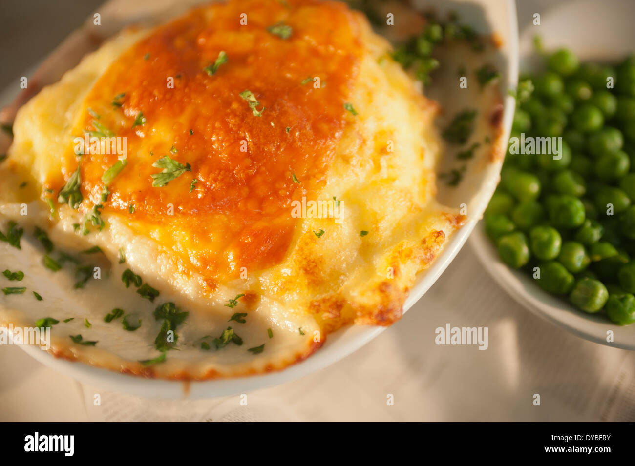 Fish and potato pie with a cheese topping and a side serving of garden peas. - Stock Image