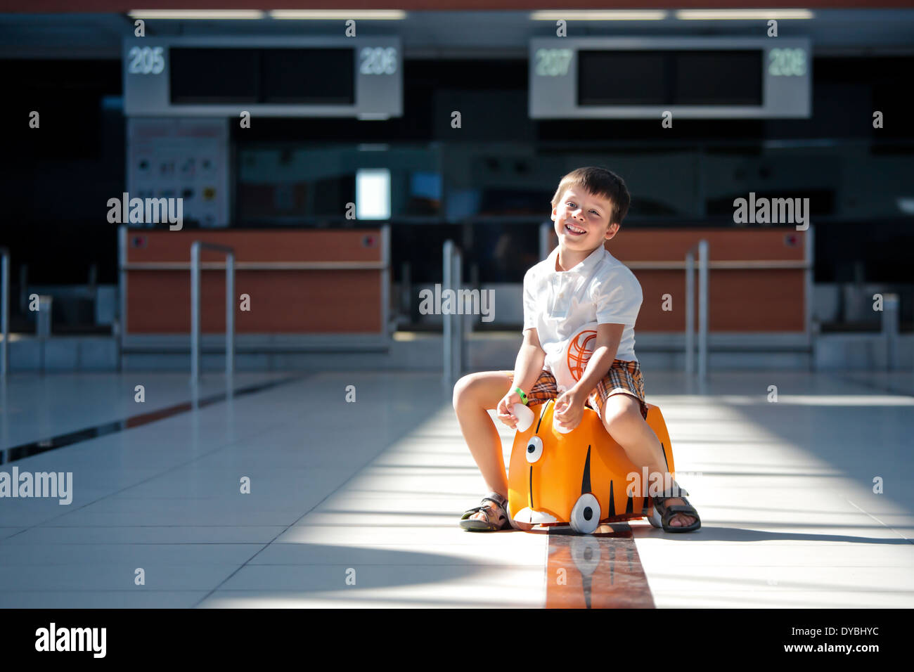 Cute little boy with orange suitcase at airport - Stock Image