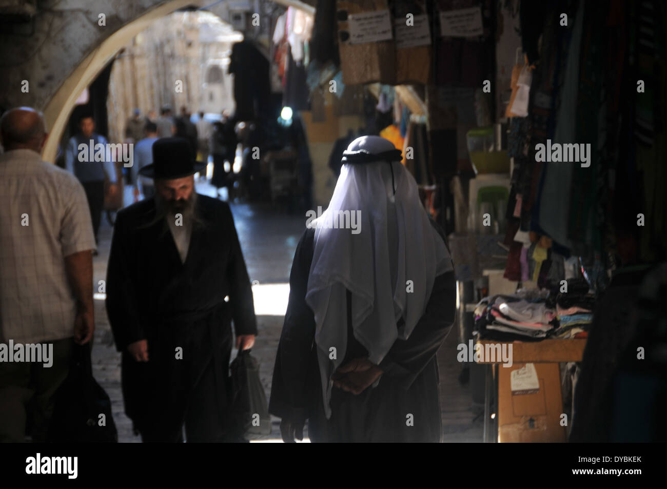 Jewish and Muslim men cross each other, walking in a narrow alley of the Muslim quarter, Old city of Jerusalem, Israel - Stock Image