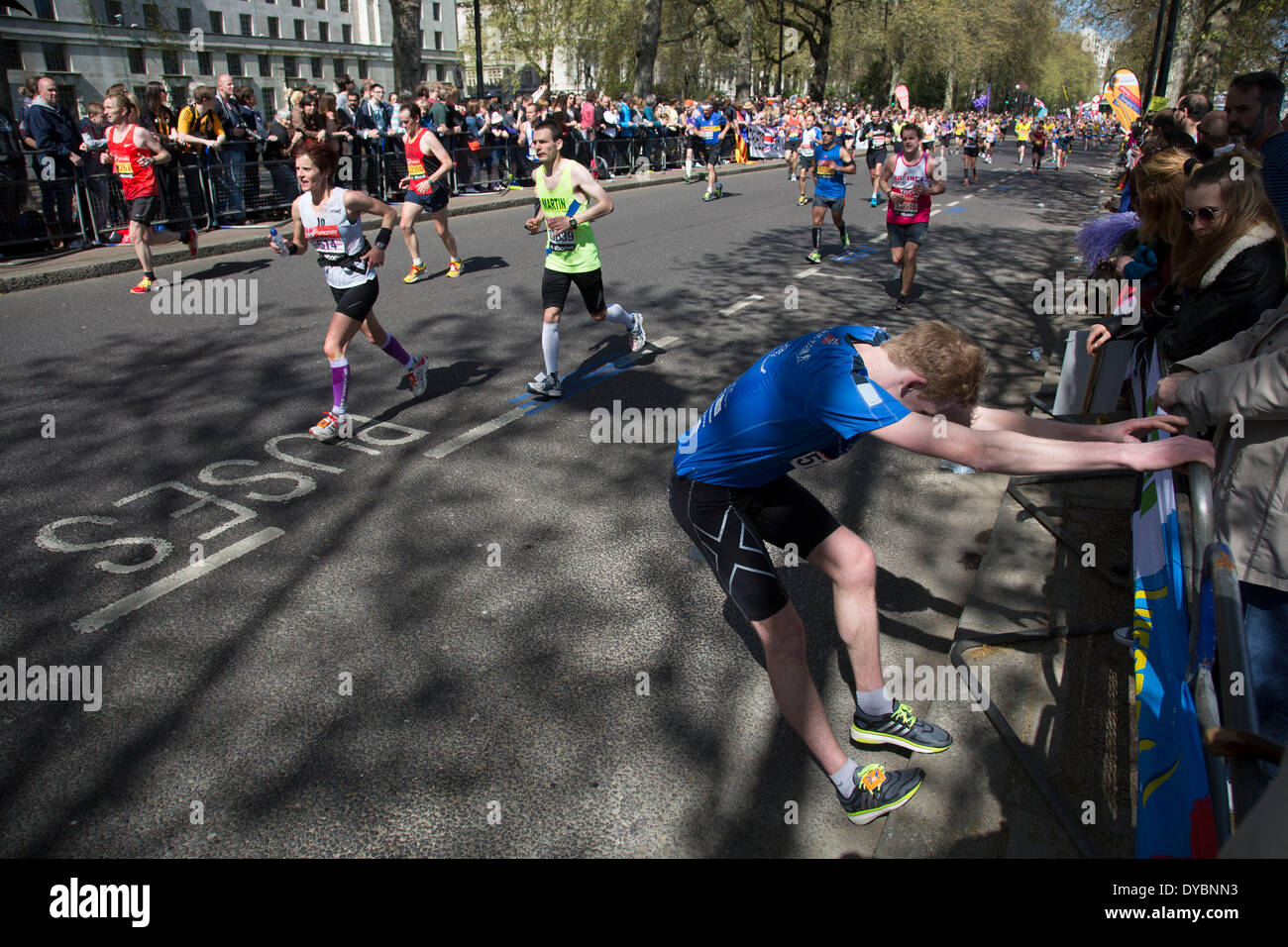 London, UK. 13th Apr, 2014. Competitors running in the main public event of the Virgin Money London Marathon 2014. These runners take part and raise huge sums fo money for charity organisations. Many runners at the later stages of the race suffer from cramp or other pain requiring stretching. Credit:  Michael Kemp/Alamy Live News - Stock Image