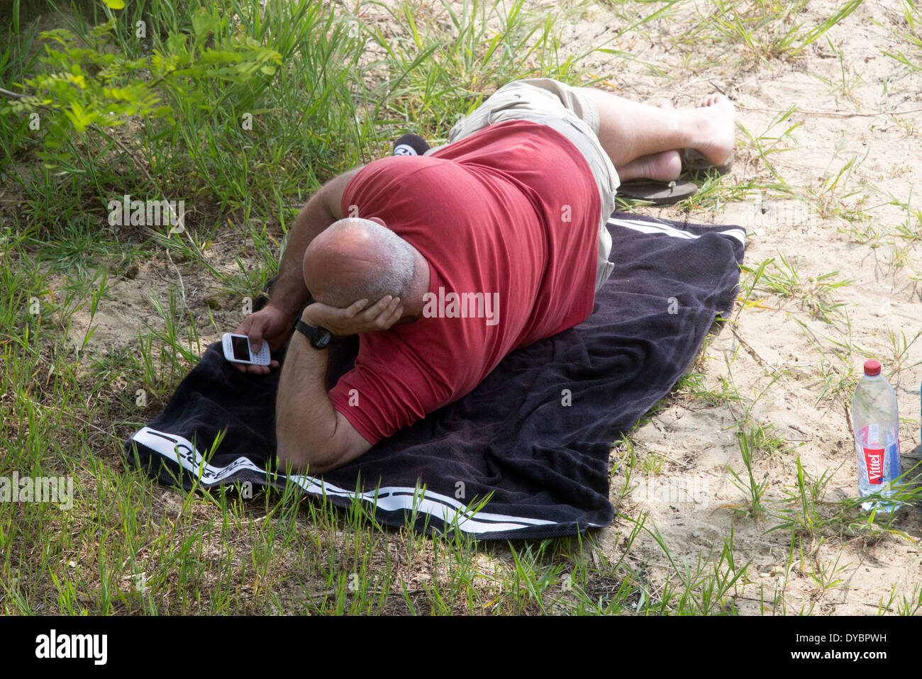 middle aged man on beach looking at phone alone - Stock Image