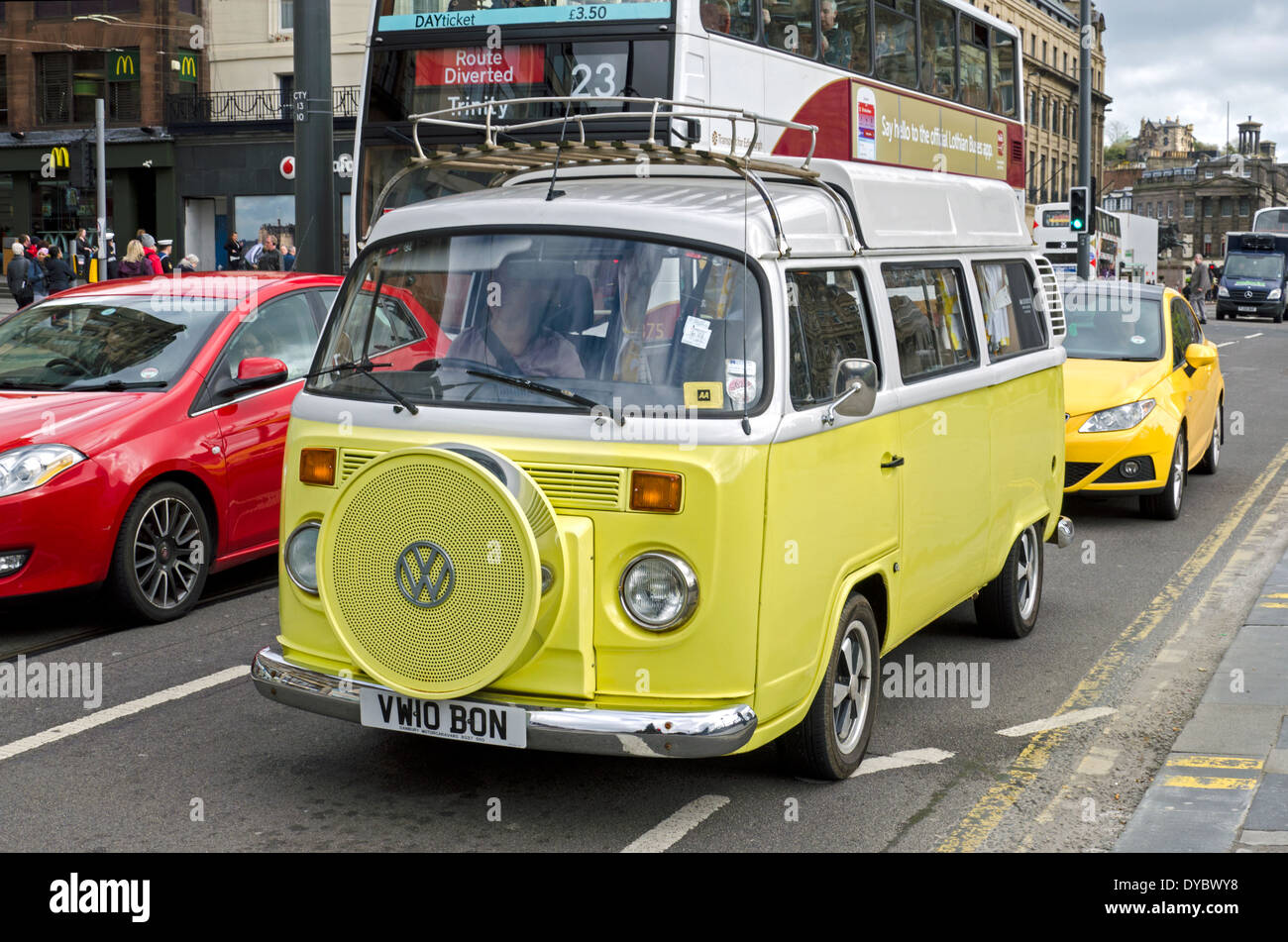 Yellow Type 2 Classic VW camper van driving along Princes Street in the centre of Edinburgh, Scotland. - Stock Image