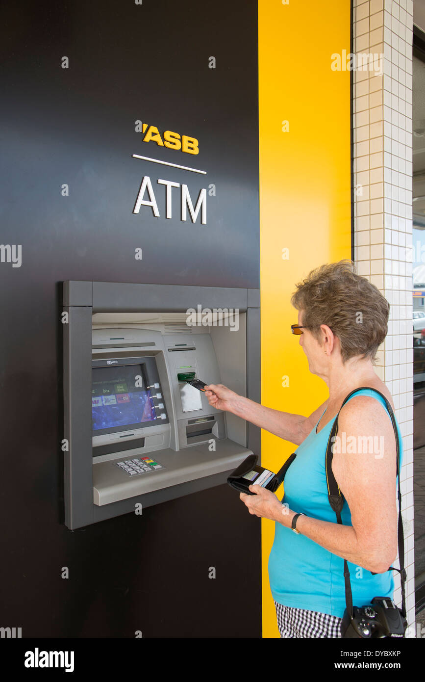 Woman using ATM at a branch of ASB Bank New Zealand Stock Photo