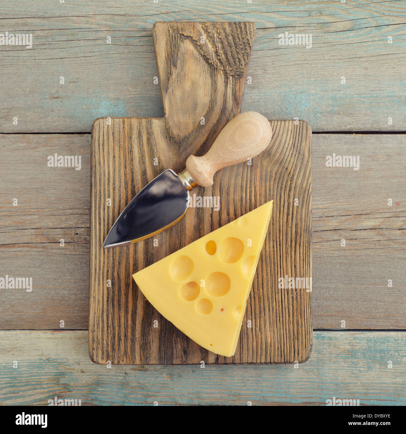 Cheese with big holes and knife on wooden cutting board - Stock Image